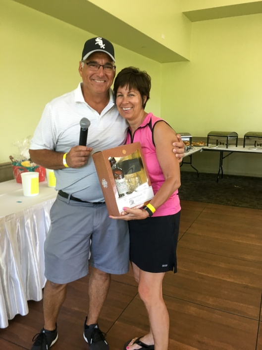 2019 Golf Outing photo of Kris and Tom Ollenburger, the event organizers, holding a silent auction prize